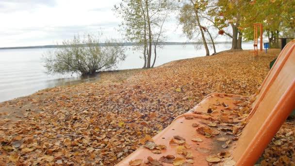 Padá listí podzimního parku na lavičce straně velkých jezer a pomalé postupné vlny na písku s žluté listy