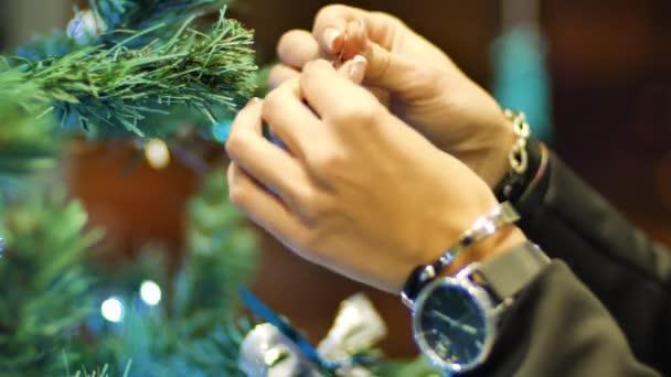 Žena ruce visící koule na vánoční stromeček. Zimní svátky vánoční a novoroční výzdobu. Blikající Garland. Vánoční světýlka