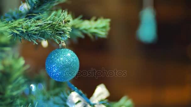 Žena ruce visící koule na vánoční stromeček. Zimní svátky vánoční a novoroční výzdobu. Blikající Garland. Vánoční světýlka.
