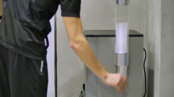 Víz öntése egy pohárba a vízhűtőből