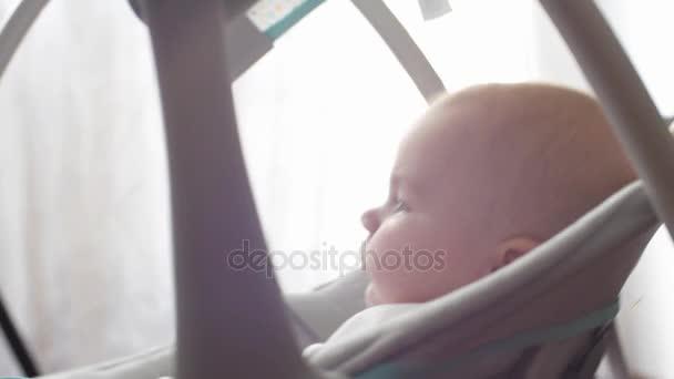 Roztomilé a okouzlující Kavkazský baby houpačky v Dětské houpačky. Dítě rozhlíží a pak se usmívá a směje se. Koncepce péče o děti, Rodičovská láska a nedostatek rodinných problémů