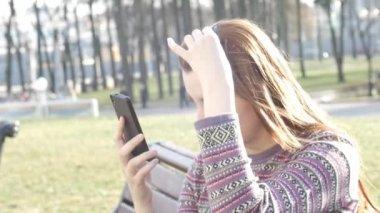 Girl makes selfie outside, sitting on bench in park