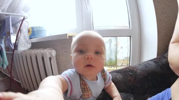 Childs pohled kamery zblízka střílel. Dítě se snaží lízat objektivu. Sladké dítě se dívá do kamery. Dítě dívá kolem sebe a pak se usmívá a směje se. Koncepce péče o děti