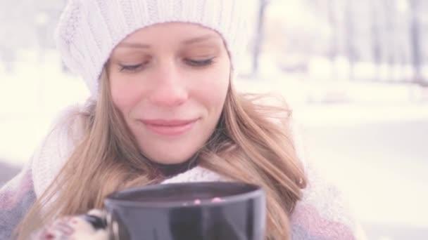 schöne junge Mädchen, die heiße Schokolade draußen im Park genießen, riechen gut und halten ein warmes Konzept der Gemütlichkeit und Behaglichkeit aufrecht. 4k uhd 3840 2160 Zeitlupe Schnellschuss