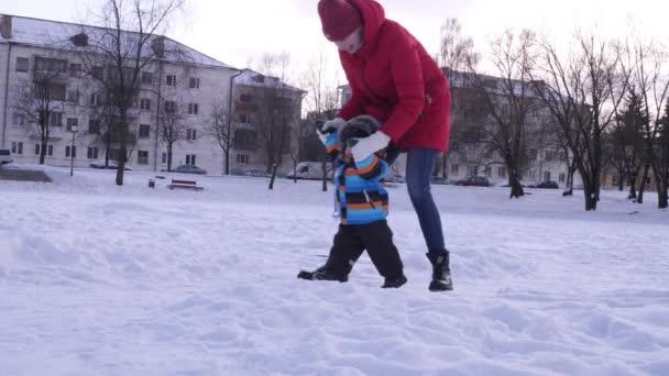 Mutter führt einen kleinen Sohn an den Armen eines Snowparks. glückliche Familie, Sonnenuntergang, Winter, Zeitlupe
