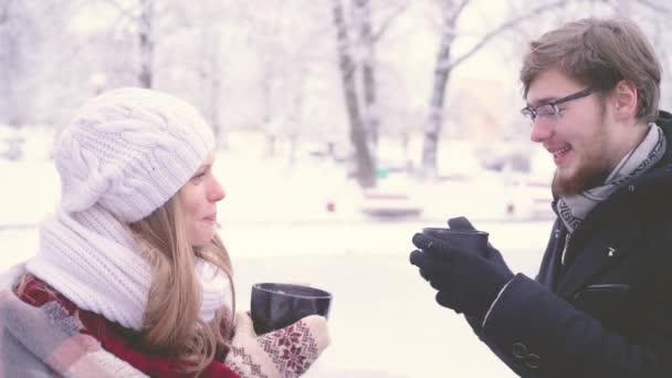 Schöne Frau und bärtiger Mann reden und trinken heißen Kakao aus Tassen in ihren Händen im Winter Park. 4 k Seite Ansicht Closeup Aufnahmen.