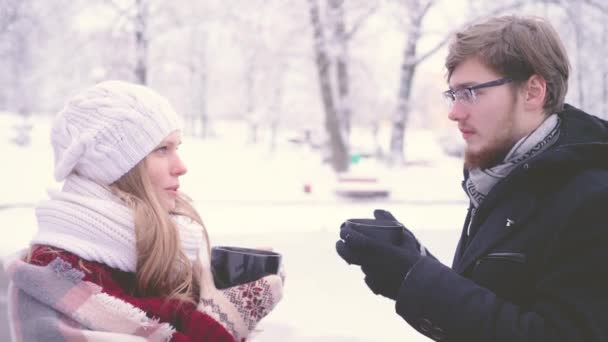Beautiful girl and bearded man talking, happy laughthing and drinking hot cocoa from cups in their hands in the winter park. 4K side view closeup footage.