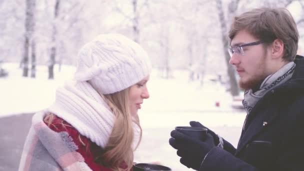 Krásná dívka a vousatý muž mluví a pití horké kakao z kelímků v jejich rukou v zimní park, se usmívá a hledat v každé jiné poháry. 4 k boční pohled detailní záběry.