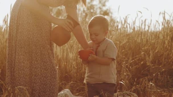 Familienatmosphäre, fröhliche Frau mit Kind gießt Milch in Gläser und trinkt während eines Familienpicknicks und genießt die Erholung im Freien aus nächster Nähe. 3D-Darstellung
