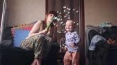 kisfiú játszik az anyjával, aki szappanbuborékokat fúj, miközben a gyerek boldogan mosolyog, miközben elkapja őket a szobában egy lassított felvételen 4K videó