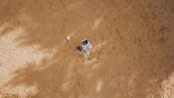 Panoráma madarak szem előtt tartva forgó kamera egy anya és fia ül árnyékában fák homokos strandon forró napos nyári napon. Nyaralás és nyaralás koncepció légi felvétel 4k videó.