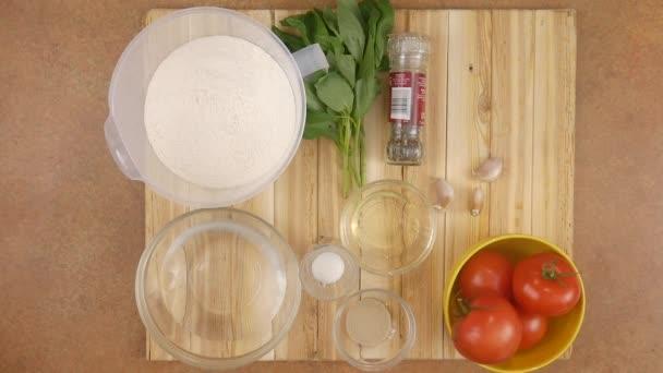 kuchařky ruce střídavě odstraňují všechny ingredience pro přípravu sýrové feferonkové pizzy z dřevěného podnosu. Top view time lapse 4k video.