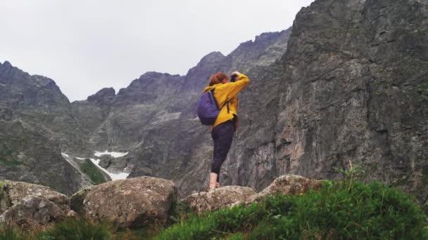 Eine Reisebloggerin in gelber Jacke mit blauem Rucksack fotografiert eine wunderschöne Berglandschaft mit Digitalkamera. Reise- und Blogging-Konzeptvideo in Zeitlupe Rückansicht 4K.
