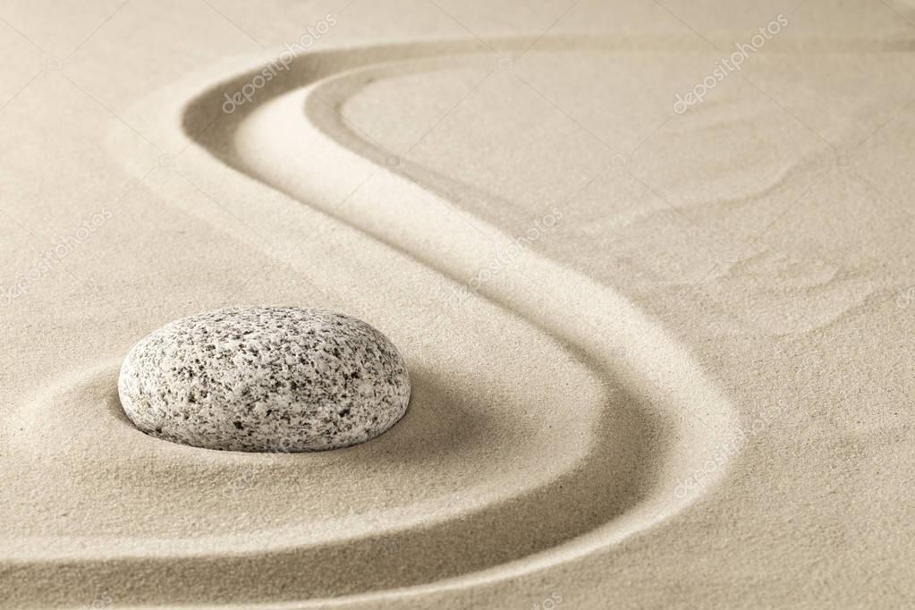 zen meditation stone in sand