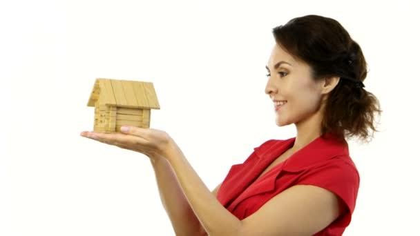 glückliche Frau hält ein kleines Haus in ihren Händen