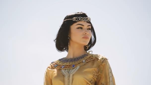 Krásná žena s módní make-up a účes jako egyptská Královna Kleopatra venku proti pouštním větrného počasí