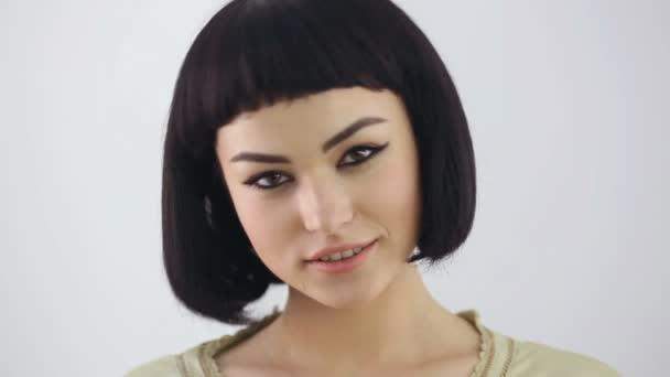 Usměvavá dívka s Kleopater make-up a účes pózuje ve studiu
