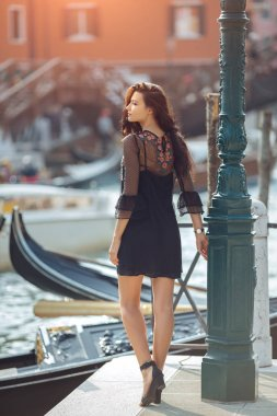 Travel tourist woman on pier against beautiful view on venetian chanal in Venice, Italy.