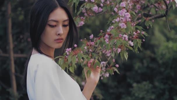 Asijské žena venku na jaře proti květ květ