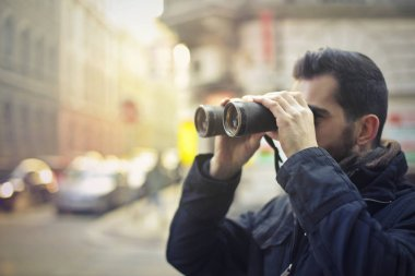 man in a city with binoculars