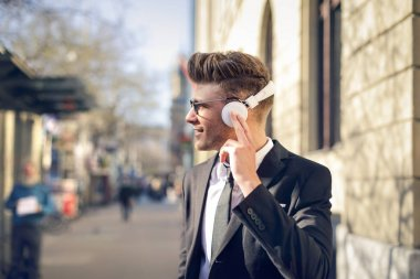 Young businessman listening to music with headphones