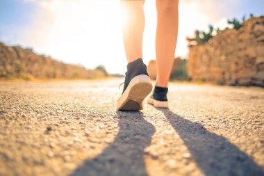 Legs walking on the pavement at sunset