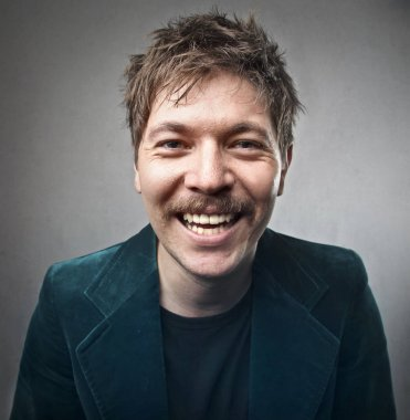 Elegant man with mustache smiling inside