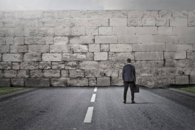 Businessman facing a huge wall on highway