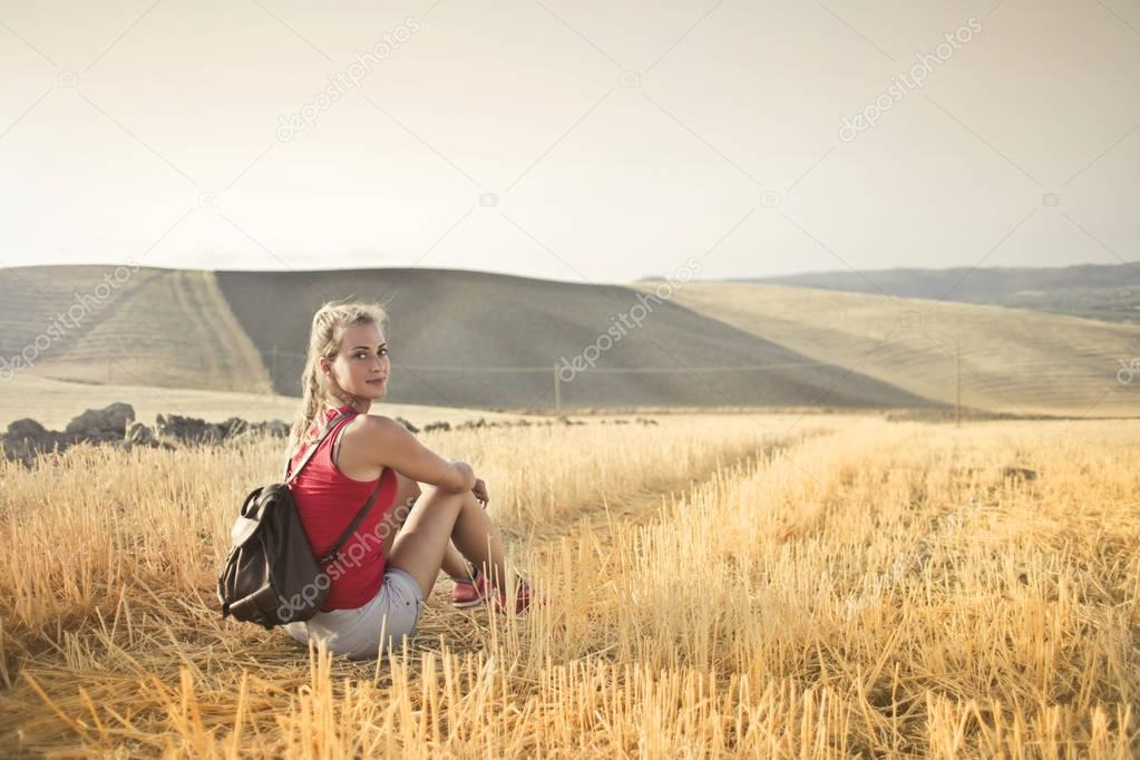 Girl sitting in a field in the countryside
