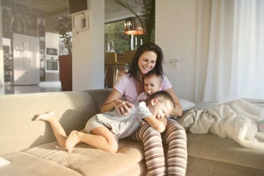 Mom sitting on a sofa with two children