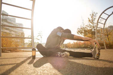 Sporty man doing stretching in a park