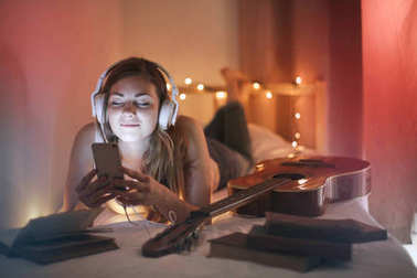 A girl relaxing on her bed listening to music with headphones