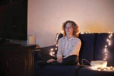 Caucasian blond guy sitting one a sofa an watching television surrounded by fairy lights