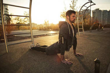 Young caucasian man with headphones doing yoga in an urban park
