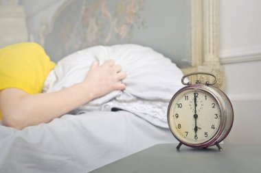 man in bed hearing the sound of the alarm clock