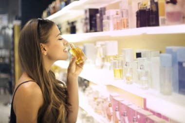 Girl smelling a parfume in a shop