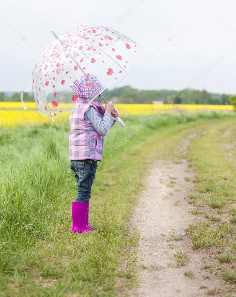 little girl with umbrella in spring nature