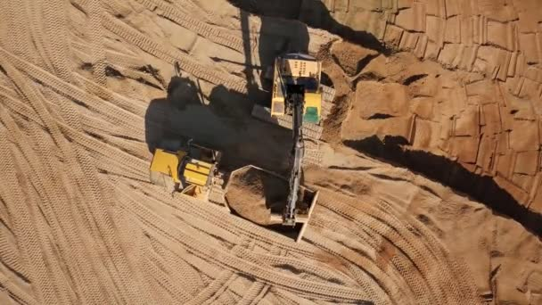 Bagger gräbt Sand aus und lädt ihn in einen LKW.
