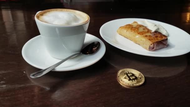 Capuccino, pancake con panna acida e bitcoin oro moneta sul tavolo in caffetteria panorama da sinistra a destra