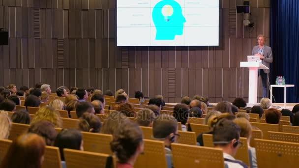 Publikum naslouchá přednášejícímu