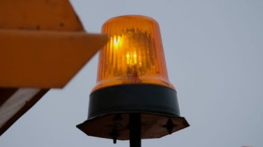 Rotating orange flash light at the road sweeper
