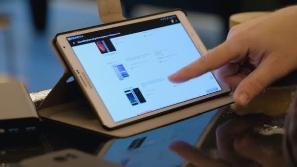 Muž zkoumání Tesla společnosti stránky pomocí počítače tablet pc v kavárně.