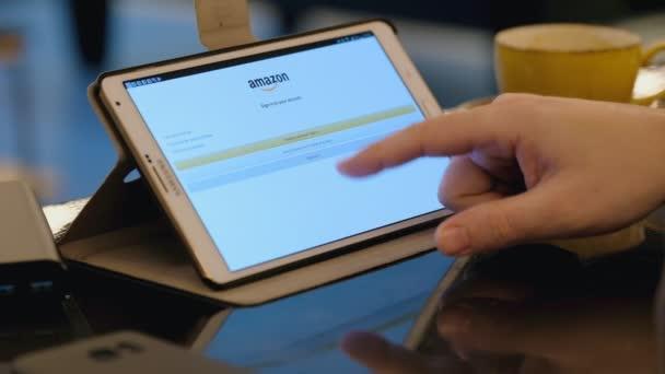 Online nakupování na Amazonu webu pomocí tblet Pc v kavárně