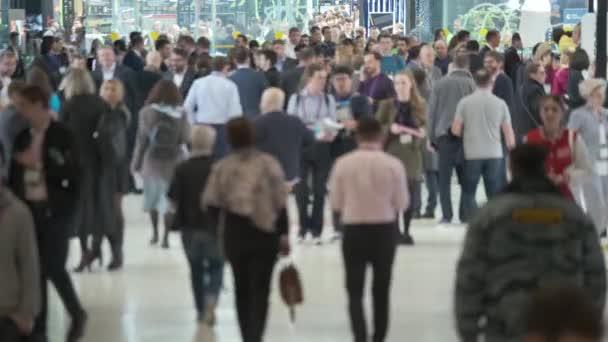 Dav lidí kráčejících dovnitř, popředí je rozostřené,