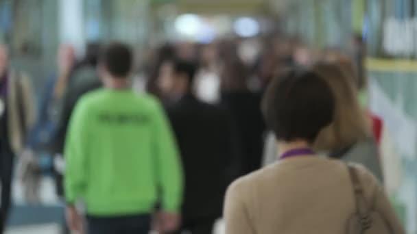 Crowd of people walking indoors, defocused,
