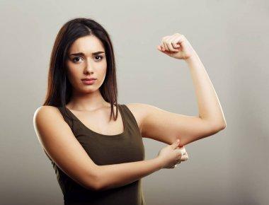 Young woman pinching arm fat skin