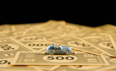 CALDWELL, IDAHO/USA - APRIL 25, 2107: Car from the game of Monopoly up against a stack of bills stock vector
