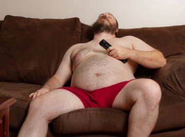 Man sleeping on the couch with remote in hand