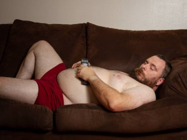 man isolating by sleeping on the couch