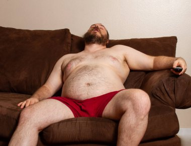 overweight man waiting at home bored watching TV